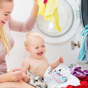 bigstock-Mother-and-baby-loading-clothe-100159337